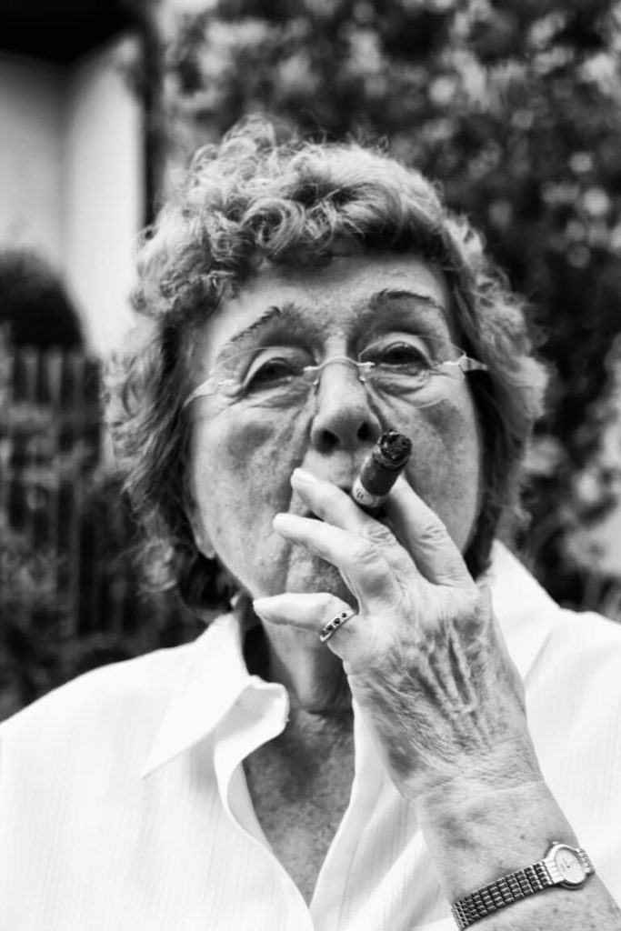 Portrait of old women who smokes a cigar